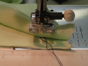 Thread is caught between stitches and can be pulled against needle before being tucked between the layers