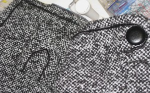 Russia braid applied by hand around outer edges of jacket, sleeve and pocket tab.