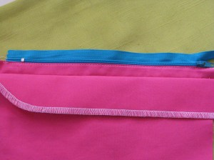 Using zipper foot, stitch on the seam allowance close to the zipper teeth and along the length of the zipper.