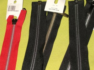 A selection of open-end zips - Left to right are large plastic teeth; wide chunky teeth; narrow teeth; open end invisible zip.