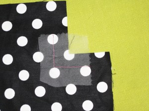 Place a small piece of silk organza over the fabric when stay stitching