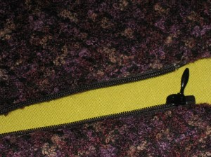 Facing side of zipper which has been sandwiched between layers.