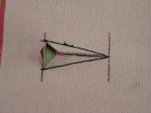 Slash buttonhole fabric to point and on the same angles as the sides of the buttonhole.