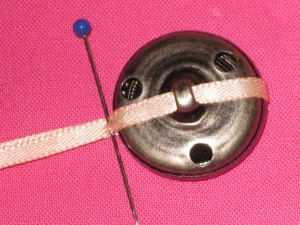 Wrap thin ribbon around the button and mark the width.