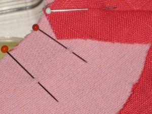 Pin facing to garment. To prevent slippage and make it easier to avoid puckers, pin at right angles to the seam and take a small bite with the pin right around where the seam line lies.