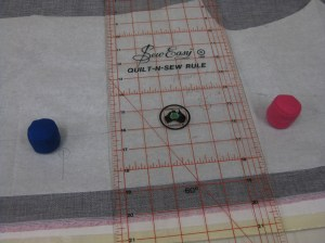 Use ruler to align grainline and weights to keep the grain line in place while pinning.