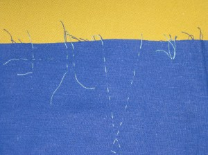 Marking by hand : L to R - crossed running stitches to mark dots; running stitch parallel to seam to mark notches; thread tracing to mark dart legs; tailor's tack to mark exact point