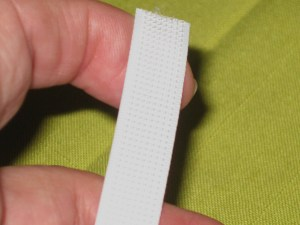 Smooth side lies against fabric; machine stitch in narrow lip on either side.
