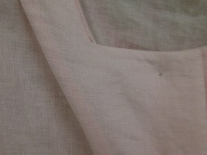 Facing the facing with lightweight fusible interfacing results in a neat, smooth finish on the inside of the garment - no shadow of overlocking can be seen from the right side of a light coloured garment.