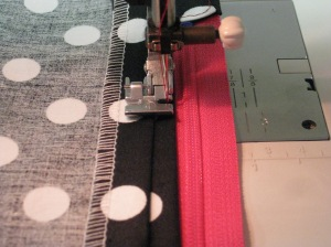 Stitch in place allowing space for zipper pull