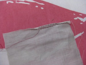 Roll under one third of hem width. Hand stitch in the fold and another third below the cut edge.