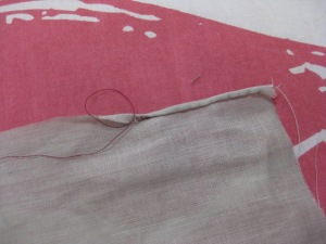 Carefully pull thread which will cause the hem to roll.