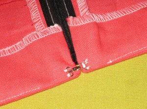 Add hook and eye and hand stitch the bottom of the facing to the seam allowance.