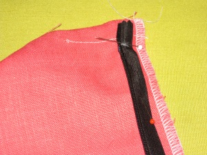 White mark indicates top of the plastic zipper stop. Teeth rest along the seam line with tape in the seam allowance.