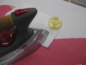 Run thread through wax and place between two sheets of paper towel; apply heat with iron and pull the thread through