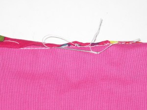 Roll folded edge back slightly. Hand stitch catching the bias just under the folded edge.