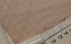 Use cutting board markings to assist in pinning fabric on grain